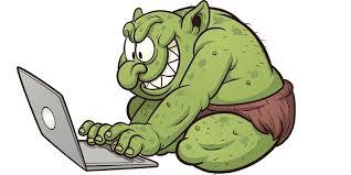 ilustracja przedstawiajaca zieonego usmiechnietego trolla przy laptopie