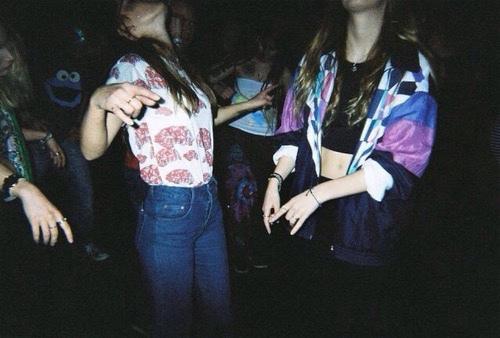 fotografia przedstawia sylwetki tańczących dziewczyn w kolorowych strojach