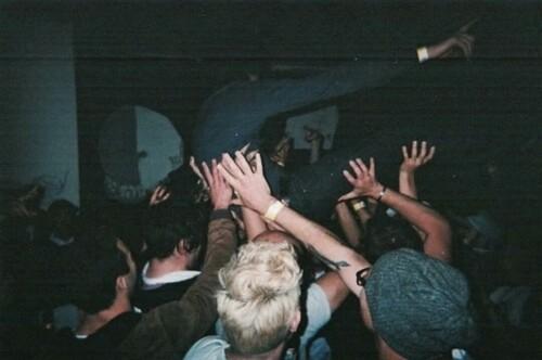 Zdjęcie jest zrobione przez osobę stojącą w tłumie. Jest trochę rozmazane. Widać na nim młodych ludzi, bawiących się na imprezie.