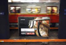 Plakat przedstawiający świnię w klatce w warszawkim metrze