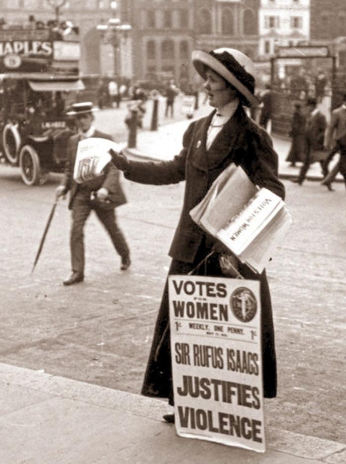 Zdjęcie w sepii pokazujące kobietę w płaszczu z tabliczką Vote for Women