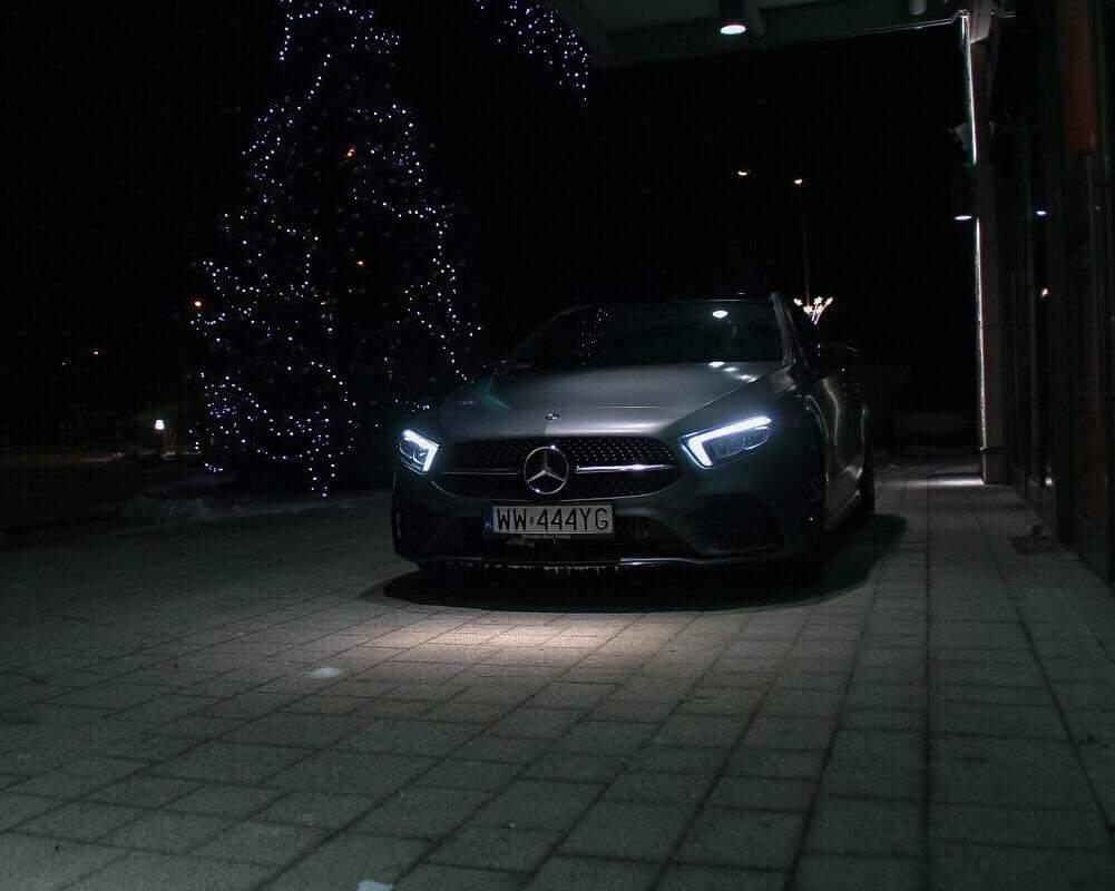 Zaparkowany samochód z włączonymi światłami
