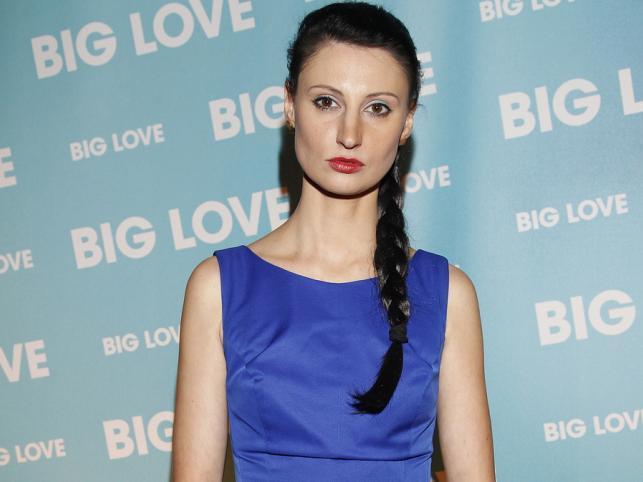 Mloda kobieta ubrana w kobaltowa sukiene na niebieskiej sciance znapisem big love