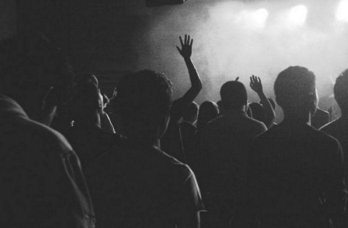 czarno-białe zdjęcie przestawiające tłum ludzi stojących tyłem, bawiących się na imprezie