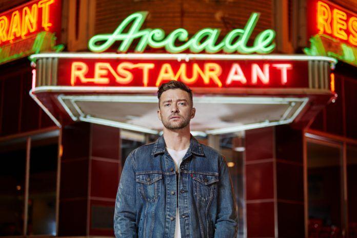 Chłopak stojący przed neonem na budynku