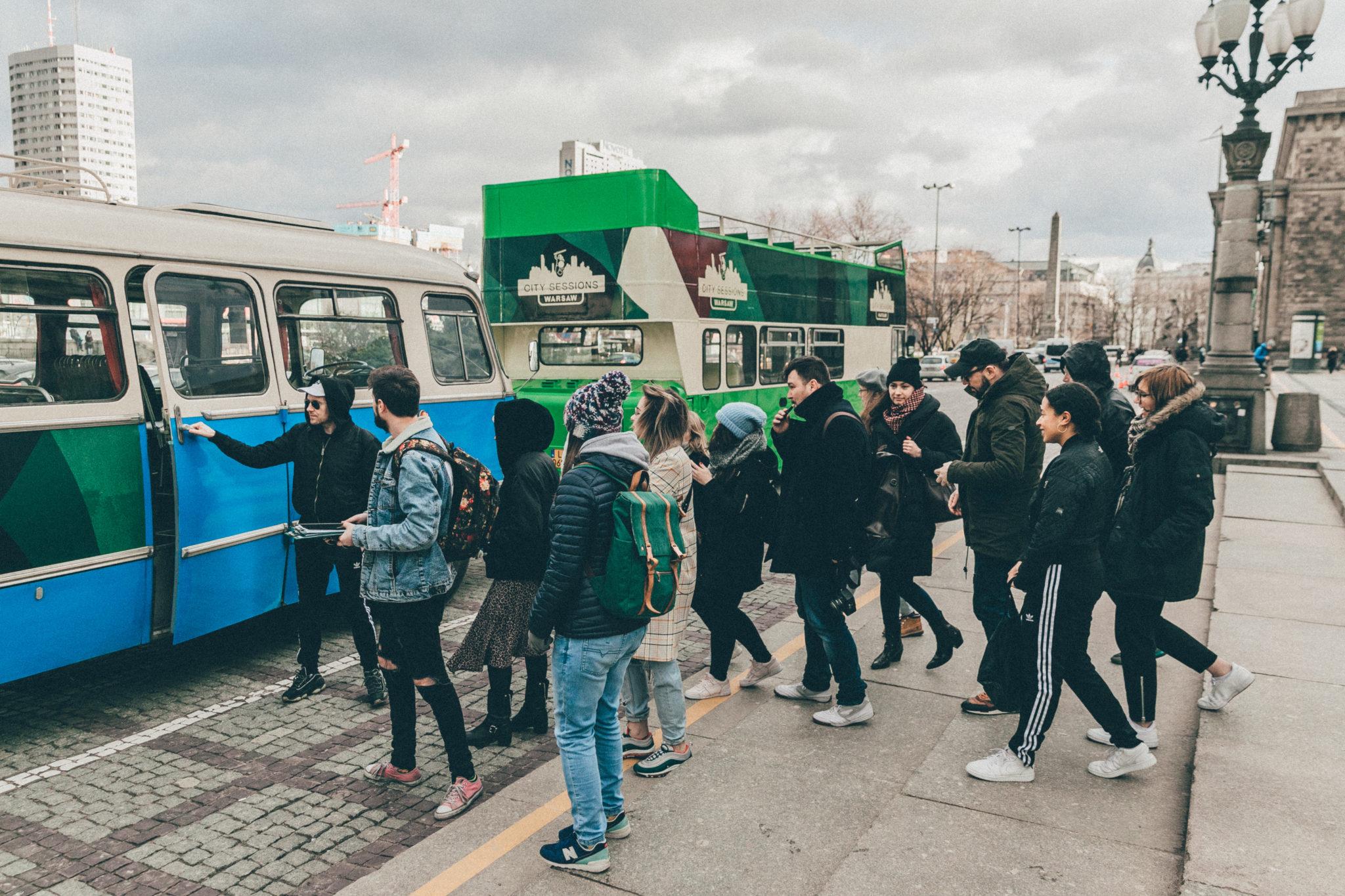 Grupa ludzi stojąca przed busem