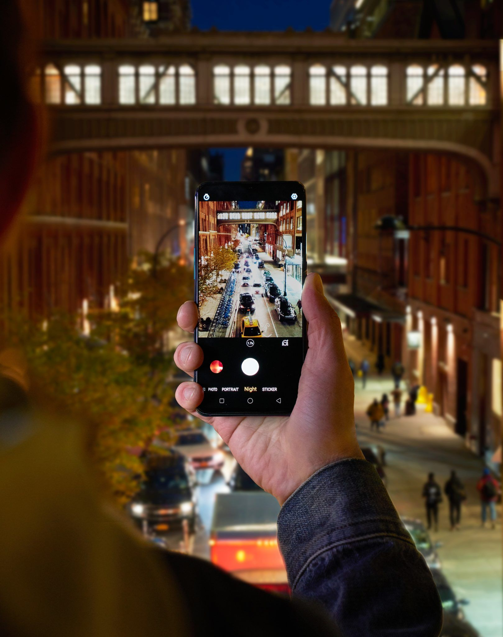 Ręka trzymająca telefon z widokiem miasta nocą w tle