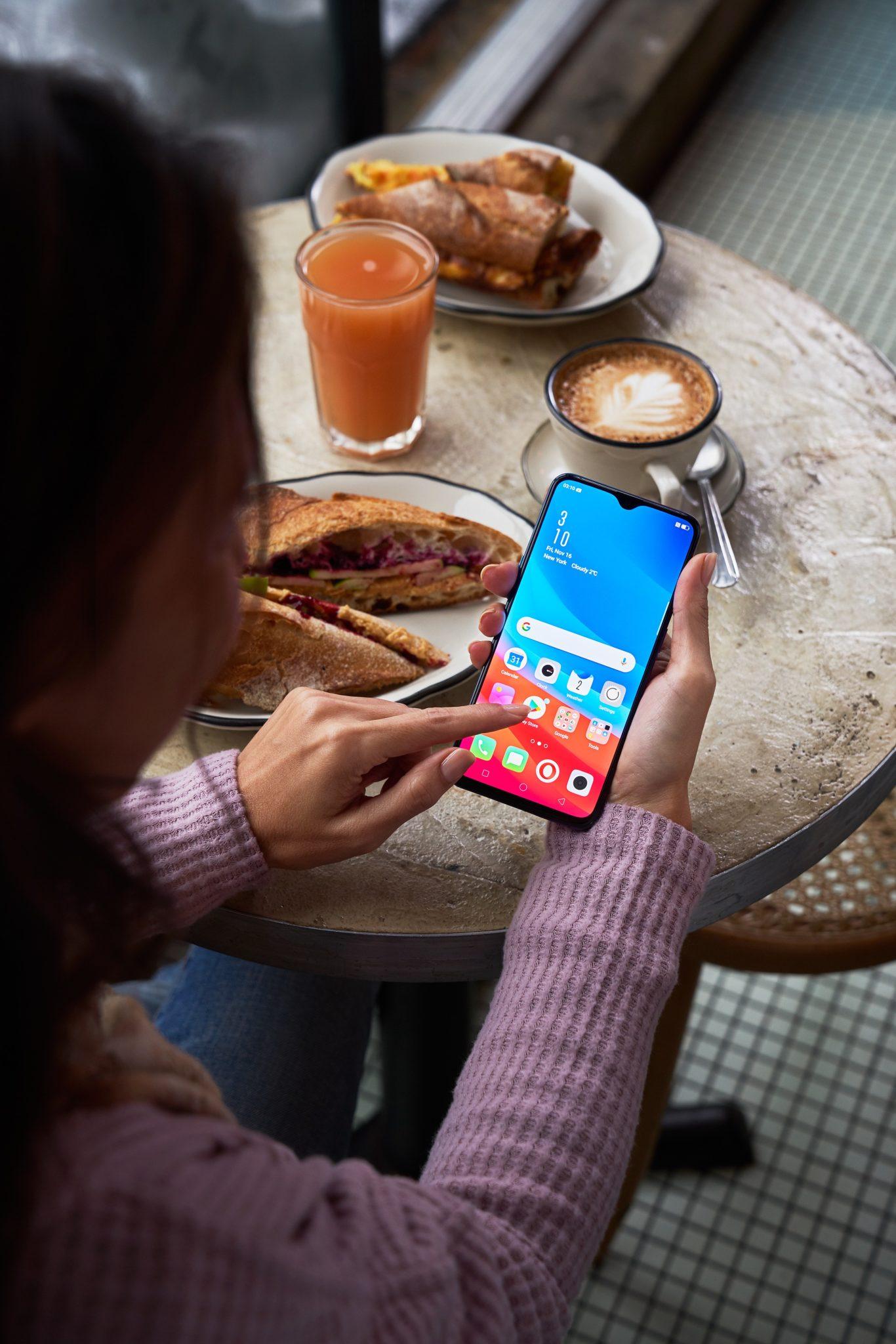 Dziewczyna klikająca na telefon przy śniadaniu