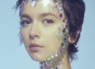 Portret dziewczyny z przyklejonymi na twarzy klejnocikami na niebieskim tle