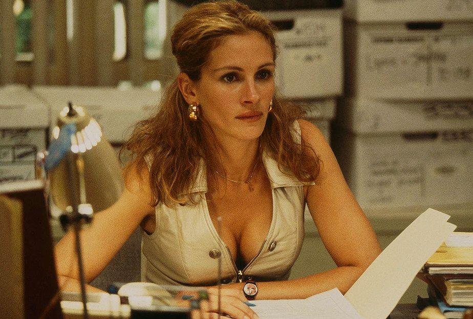 Na zdjeciu widzimy kobiete siedzaca za biurkiem z wielkim dekoltem odslaniajacym piersi