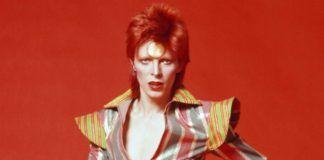 Mężczyzna w kolorym kombinezonie na czerwonym tle