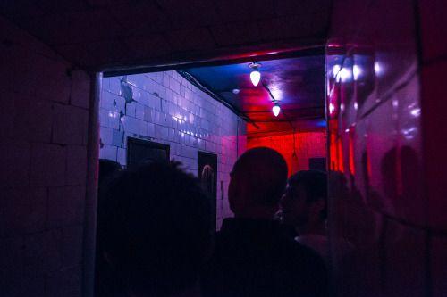 zdjęcie przestawia ludzi stojących w kolejce (prawdopodobnie do toalety), przed nimi znajduje się ściana z białych kafelków, a kolorowe lasery nadają czerwono filetowy urok tej fotografii
