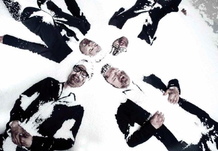 Zespół Muchy - zdjęcie na śniegu, mężczyźni ubrani w garnitury.