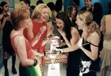 Cztery dziewczyny stojące przy stoliku z drinkami