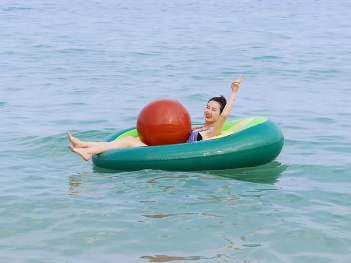 ponton w kształcie awokado na morzu z dziewczyną w środku