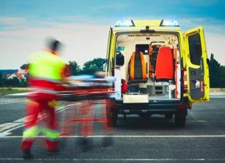 otwarta żółta karetka, do której ratownik medyczny, przenosi rannego