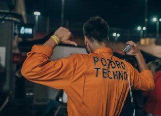 Chłopak w pomrańczowej koszuli z napisem Pozdro Techno