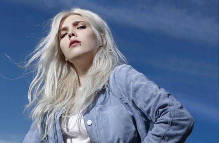 Blondynka w jeansowej koszuli na tle błękitnego nieba