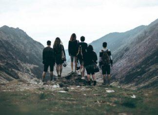 Grupa ludzi stojąca tyłem do obiektywu na górze