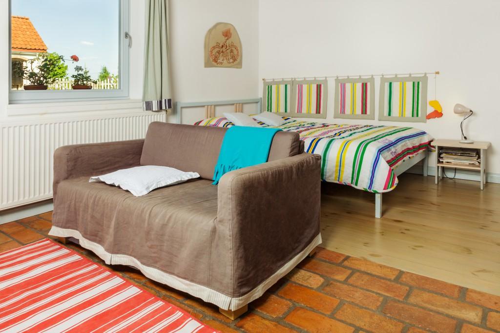 sypialnia z dużym łóżkiem i kanapą