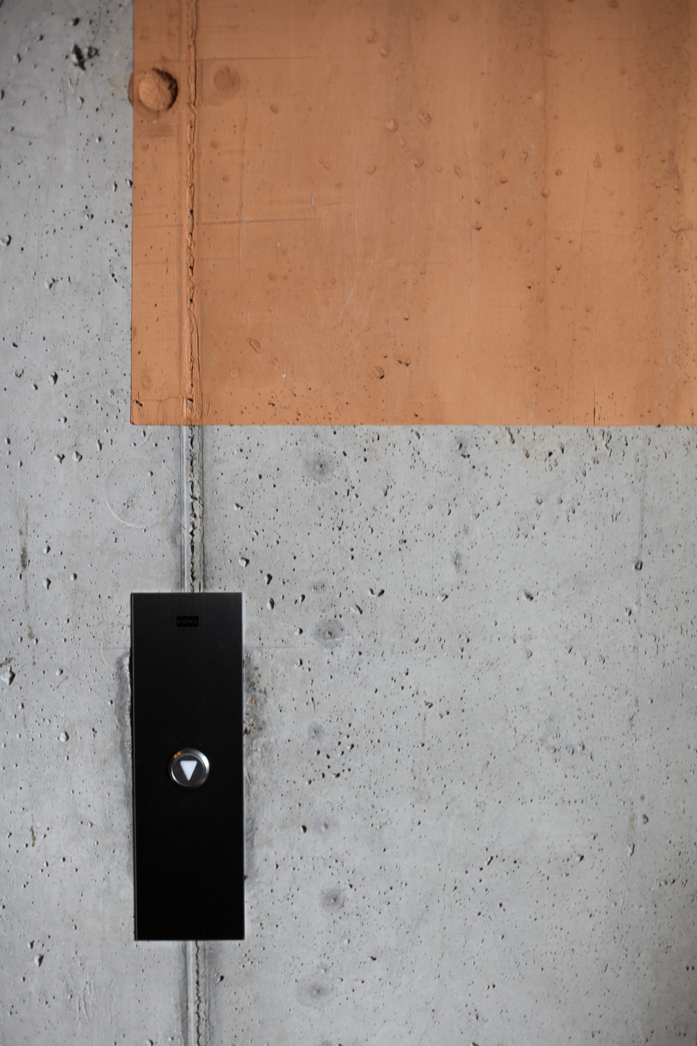 Fragment betonowej ściany i przyscisk windy