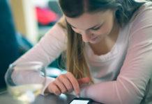 Dziewczyna siedząca z telefonem przy stoliku