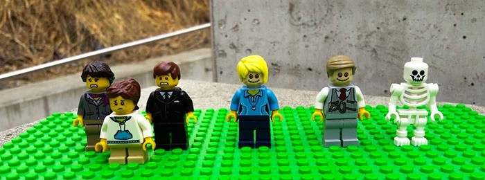 Klocki lego przedstawiające rodzinę ubraną na czarno, trupa i pracownika zakładu pogrzebowego
