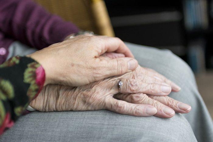 zdjęcie ukazuje dłoń starszej osoby, na której młoda osoba trzyma swoją rękę
