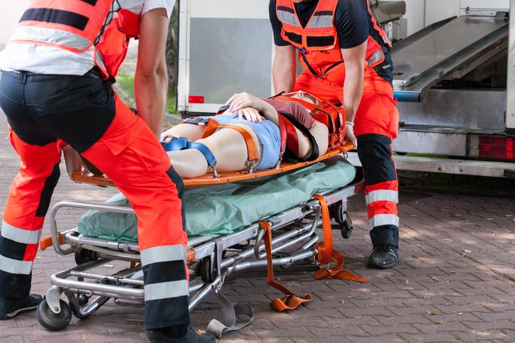dwaj ratownicy medyczni wnoszą rannego do karetki