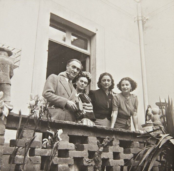Czarno-białe zdjęcie przedstawiające trzy kobiety i mężczyznę na werandzie