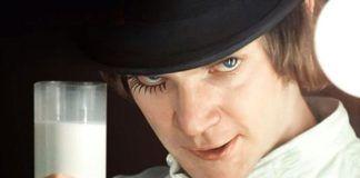 Mężczyzna w czarnym kapeluszu i białej koszuli ze szklanką mleka w dłoni