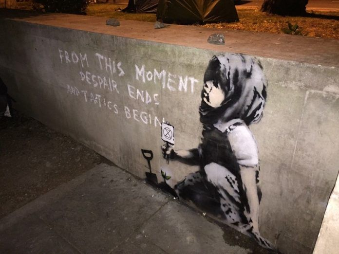 Mural przedstawiający dziecko z banerem protestacyjnym