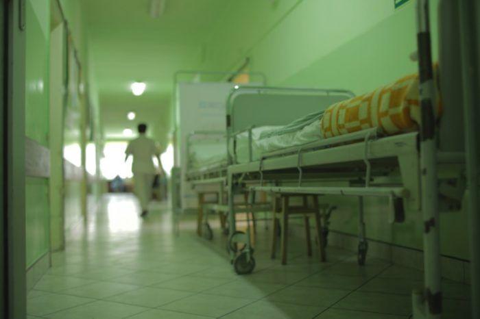 zdjęcie przedstawia łóżko szpitalne i korytarz