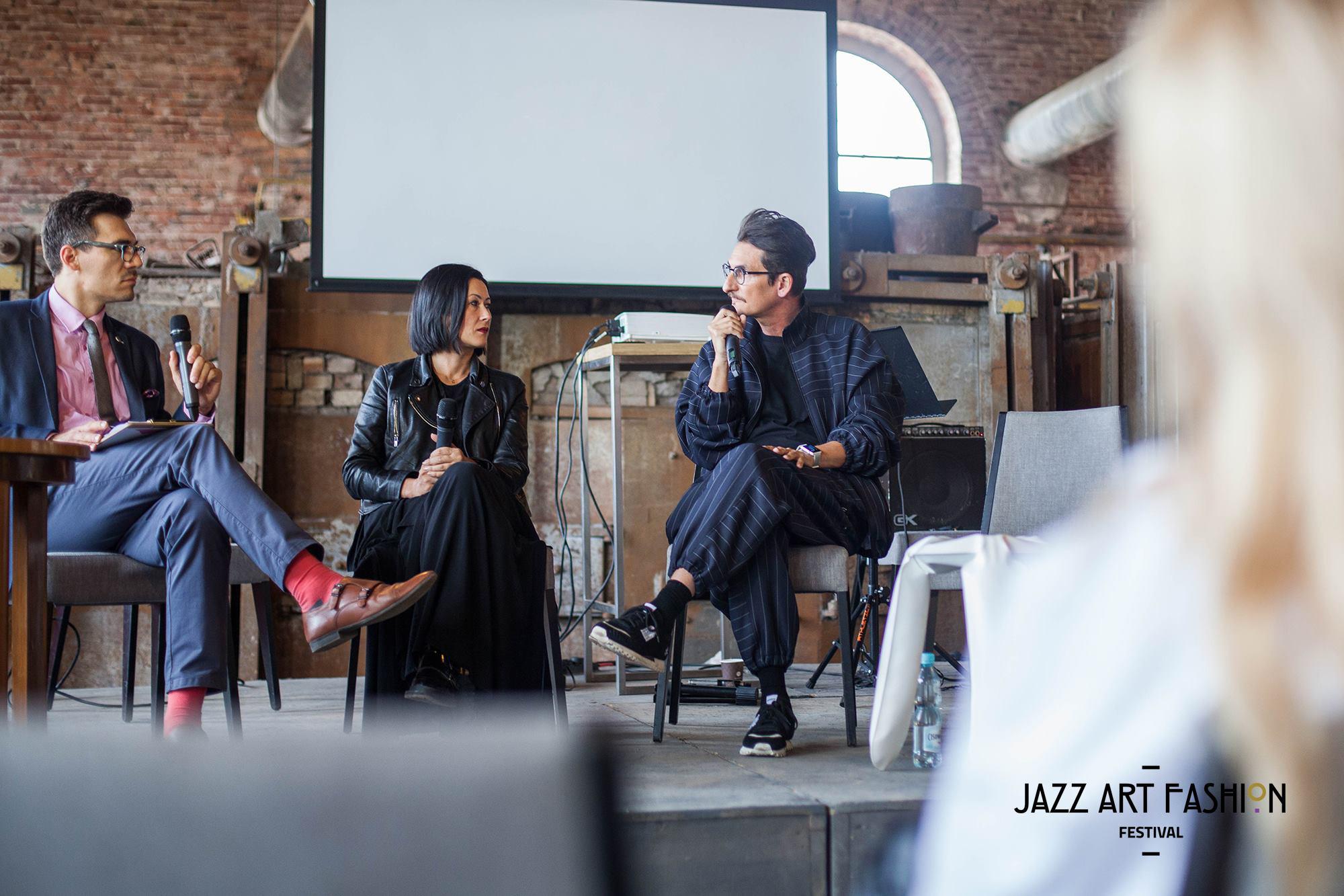 Trzy oosby siedzące na scenie podczas panelu dyskusyjnego