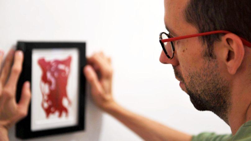 Meżczyzna wieszający obrazek na ścianie