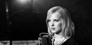 Czarno-białe zdjęcie kobiety stojącej przy mikrofonie