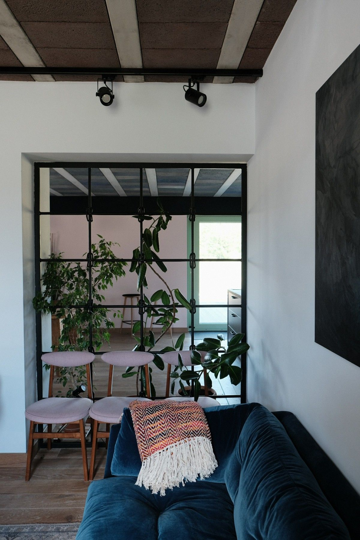 Wnętrze domu z granatową kanapą i roślinami