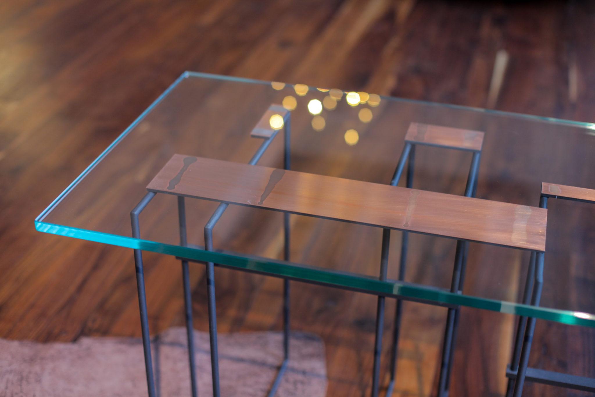 Szklany stolik z miedzianymi elementami na drewnianej podłodze
