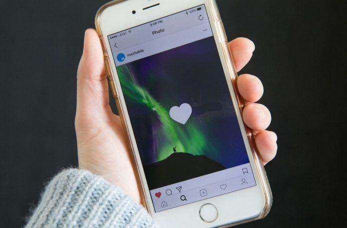 Ręka trzymająca telefon z otwartą aplikacją Instagram