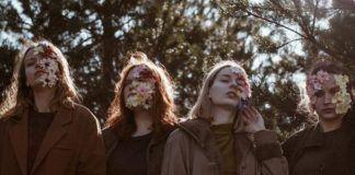Cztery dziewczyny stojące w parku z kwiatami na twarzy