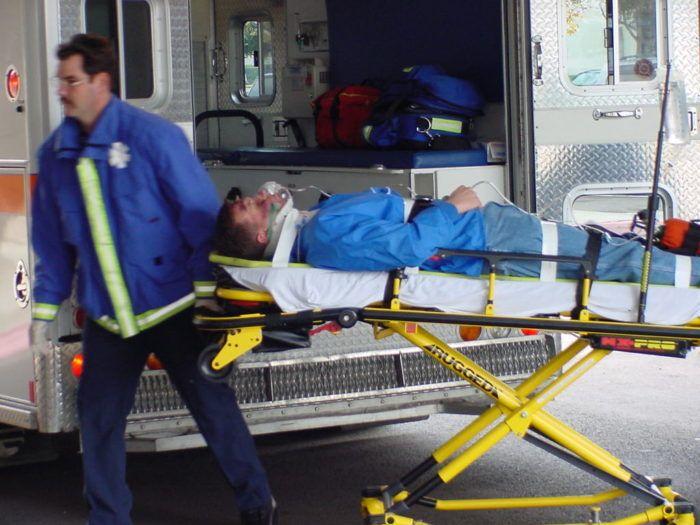 ratownik medyczny przewozi rannego na noszach