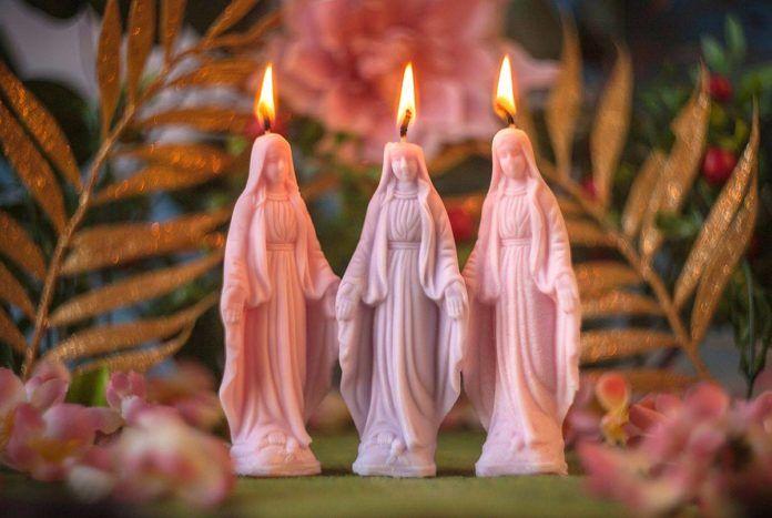 Świeczki w kształcie figurek Maryi na tle zieleni