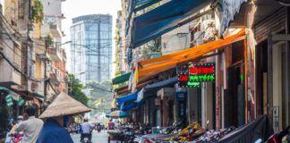 Widok uliczki w wietnamie: widać skutery i kobietę w kapeluszu