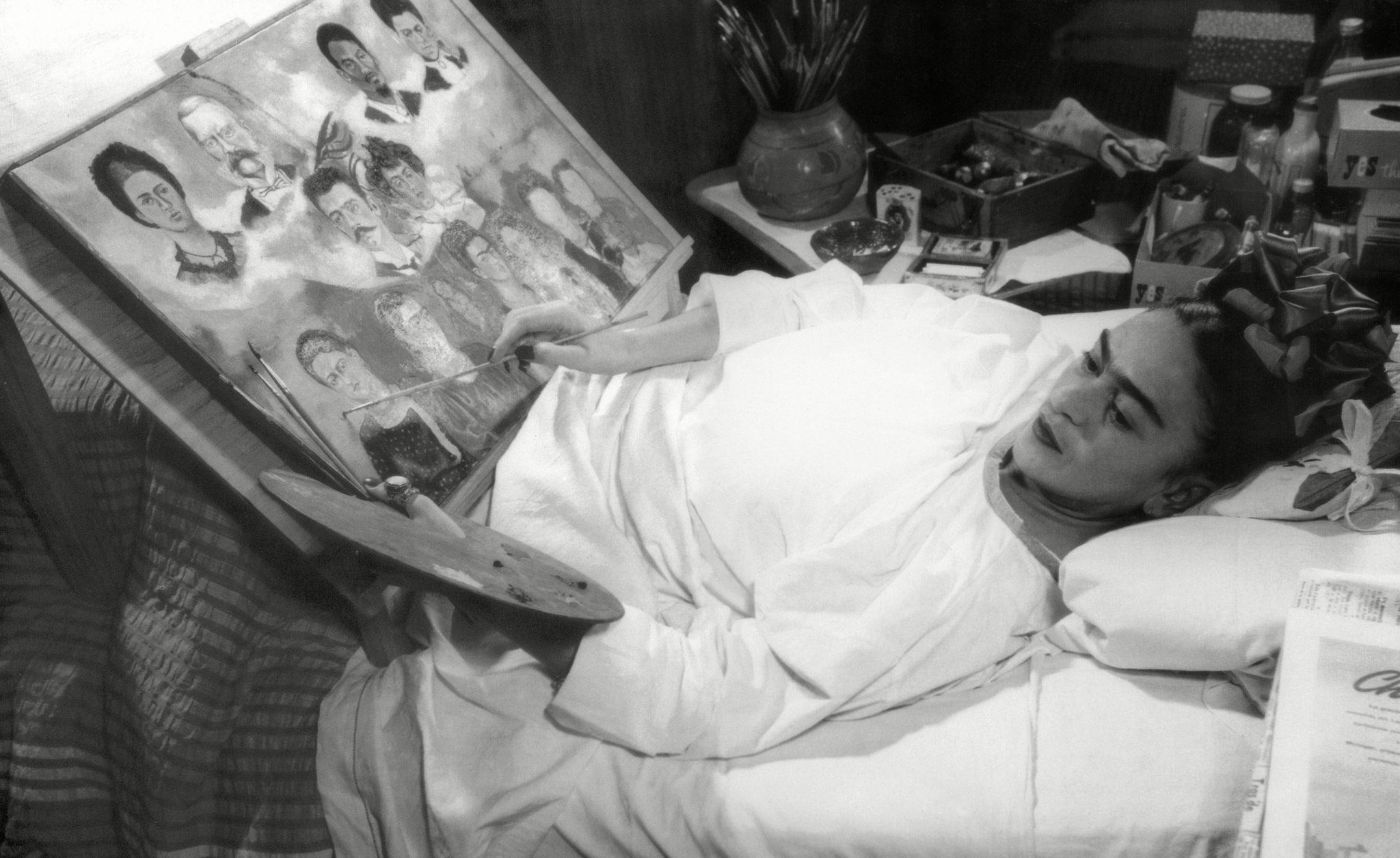 Kobieta leżąca na łóżku, malująca obraz