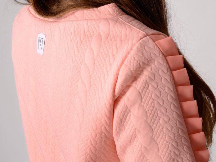 Kobieta w różowej bluzce z falbankami
