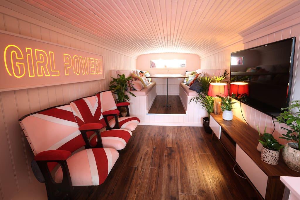 Wnętrze busa z kanapami i neonem