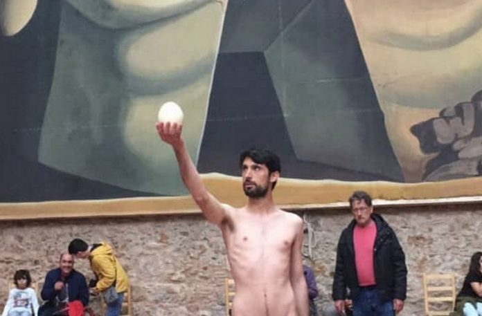 Nagi mężczyzna trzymający jajko