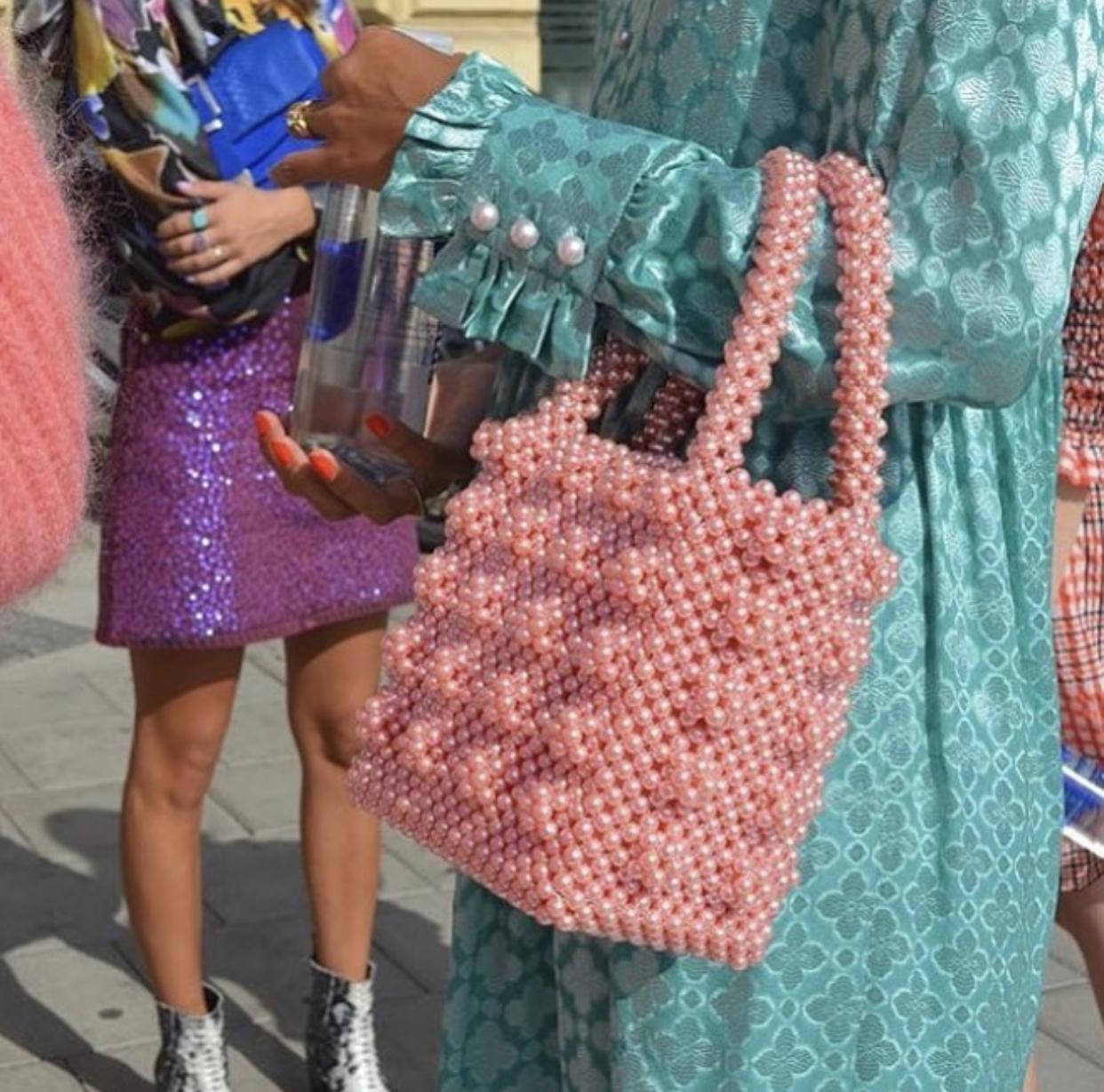 Dziewczyna trzymająca torebkę z różowych koralików