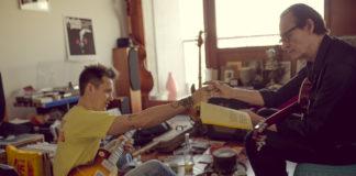 Dwóch mężczyzn z gitarami podających sobie ręke