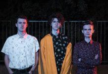 Trójka chłopaków stojąca na tle ogrodzenia nocą